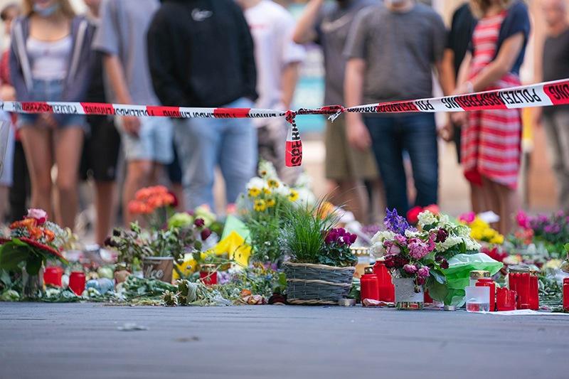 28.06.2021, Bayern, Würzburg: Trauerkerzen und Blumen liegen vor einem Kaufhaus in der Innenstadt, in dem ein Mann Menschen mit einem Messer attackiert hatte. Bei dem Angriff am 25.06.2021 hatte ein Somalier drei Frauen in einem Kaufhaus getötet. Auf der Straße und in einer nahen Bank verletzte er danach laut Polizei sechs Menschen schwer und einen leicht. Foto: Nicolas Armer/dpa
